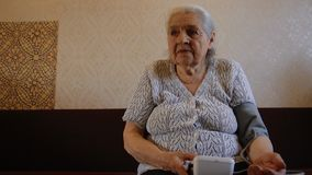 An old woman is measuring her blood pressure. Grandma`s using a tonometer. FHD stock video