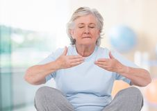 Old woman Meditating against bright background Stock Image