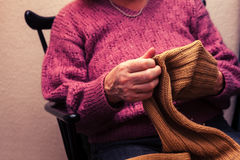 Old woman mending a jumper at home Stock Images