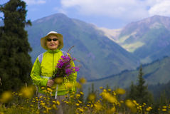 Old woman in mountain. Old woman with mountains flowers Stock Images