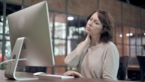 Old Woman with Neck Pain at Work. The Old Woman with Neck Pain at Work stock video footage