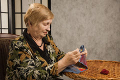 Old woman with a needle and a thread Stock Images