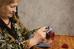 Old woman with a needle and a thread Royalty Free Stock Photo