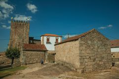 Old woman next to gothic chapels. Old woman next to the chapels of Saint Anthony and Calvary, in a sunny day at the medieval Belmonte Castle. A cute small town stock photography