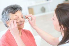 Old woman at oculist tries pair glasses Royalty Free Stock Photos