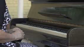 Old woman open cover and start playing the piano stock footage