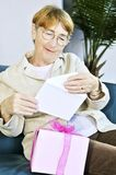 Old woman opening present Royalty Free Stock Photography