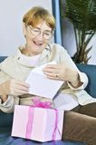 Old woman opening present Royalty Free Stock Images