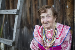 Old woman outdoors in rural areas. Happy. Royalty Free Stock Images