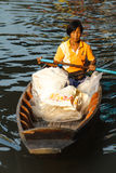 Old woman paddling wooden boat Royalty Free Stock Image
