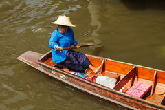 Old woman paddling wooden boat Stock Photo