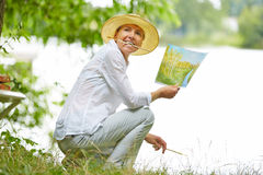 Old woman painting with brush in nature Stock Photo