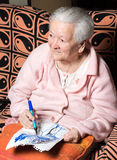 Old woman painting for fun Stock Photos