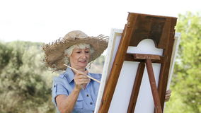 Old woman painting in the park stock footage