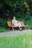 Old woman on a park bench thinking. Elder lady on a park bench in the sun Royalty Free Stock Image
