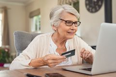 Old woman paying bills online royalty free stock image