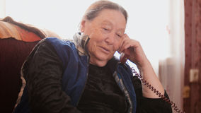 Old Woman pensioner speak landline telephone and smiling, close up. Telephoto Royalty Free Stock Photos