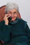 Old woman on the phone. Portrait of an old woman using a mobile phone Stock Photography