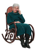 Old woman on the phone. Image of an old woman sitting  in a rocker and using a mobile phone Royalty Free Stock Photo