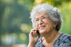 Old woman on phone. Portrait of mature woman talking on smartphone outdoor. Senior woman smiling and talking on the phone at park. Close up face of a cheerful royalty free stock image