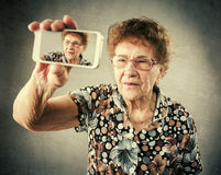 Old woman photographed yourself on the phone Royalty Free Stock Images