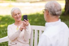 Old woman photographing man by smartphone in park. Technology, retirement and old people concept - happy smiling senior couple with smartphone photographing in Royalty Free Stock Photo