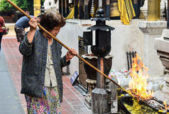 An old woman picking out the candle tears. An old woman using a bamboo stick to pick out the  dried wax candle tears Royalty Free Stock Photos