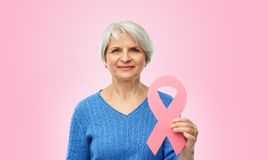 Old woman with pink breast cancer awareness ribbon. Health, charity and old people concept - portrait of smiling senior woman with breast cancer awareness ribbon stock photos