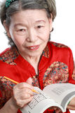 Old woman play sudoku Stock Photo