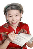Old woman play sudoku stock images