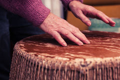 Old woman playing bongo drums Royalty Free Stock Images