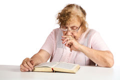 old woman in points thoughtfully looks  book Royalty Free Stock Photo