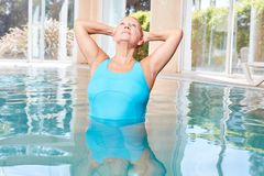 Old woman in pool doing stretching exercise in aqua gym class stock photos