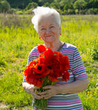 Old woman with poppies Royalty Free Stock Photos