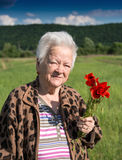 Old woman with poppies Stock Photos