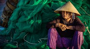 Old woman at the port. Hat, conical, net, fishing, basket, portrait, vietnam, phanrang, wait, waiting, sad, unhappy stock photography