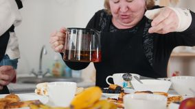 An old woman pouring tea in the cup. Mid shot stock video footage