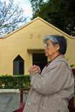Old woman pray in front of the church Royalty Free Stock Photography