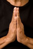 Old woman praying. An old asian woman holds her hands in prayer Stock Images