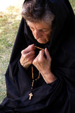An old woman is praying in the garden Royalty Free Stock Photo