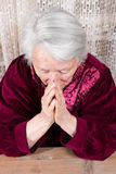 Old woman praying Stock Images