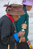Old woman praying with prayer roll in Lhasa Royalty Free Stock Images