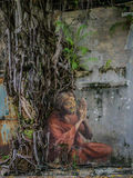 Old Woman Praying Street Art under a Tree. Street Graffiti picturing an old woman praying under a tree Royalty Free Stock Photo
