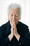Old woman praying Royalty Free Stock Image