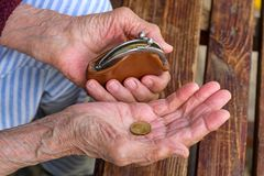 An old woman with a wallet and a coin Stock Image