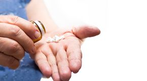 Old woman puts pills medication in her hand isolated on a white background, senior hand medication. Old woman puts pills medication in her hand isolated on a Stock Photos