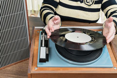 Old woman puts a vinyl record Stock Photos