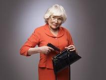 Old woman putting gun in handbag. Senior woman putting a gun in her small handbag, self defence concept royalty free stock photography