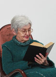 Old woman reading. Portrait of an old woman reading a black book against a gray background Royalty Free Stock Photo