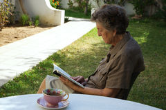 An old woman is reading a book in the garden Royalty Free Stock Photos